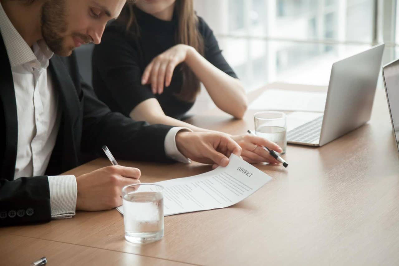 Smiling successful businessman in suit signing business contract concept, investor entrepreneur puts signature fills legal official document, customer buys insurance services, client takes bank loan