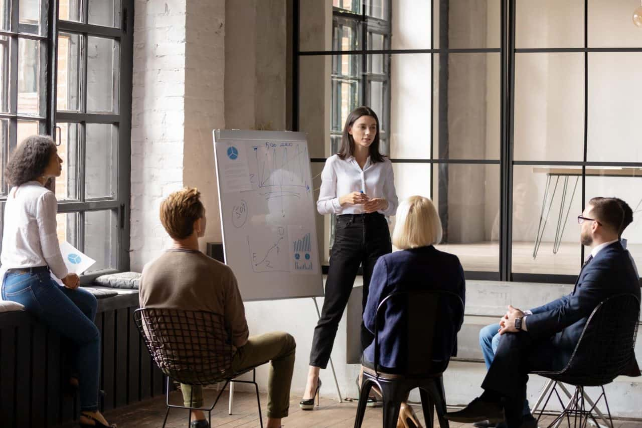Young confident ceo make forecast financial report on flip chart for diverse staff, group of workmates listen woman business trainer take part at educational meeting in modern office coaching concept